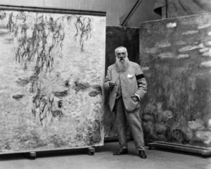 Monet standing with two of his water lily paintings